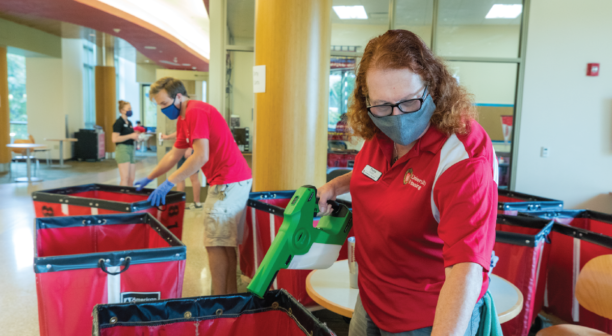 Residence Hall Facilities Staff Member Sanitizing Red Carts During Move-In