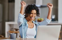 Woman cheering at a computer